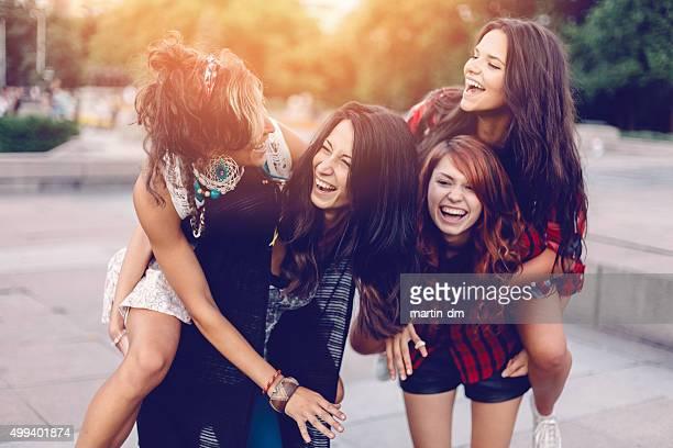Teenage girls piggyback outside