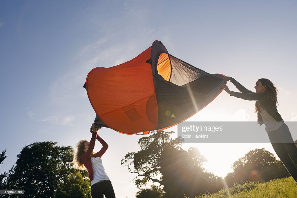 Teenage girls pitching tent in field : Stock Photo