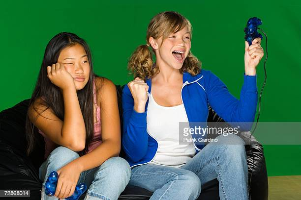 Teenage girls (12-15) playing game console, one cheering