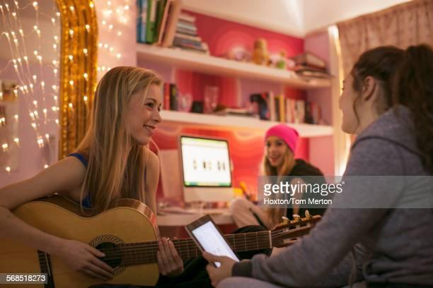 Teenage girls playing guitar and using digital tablet in bedroom
