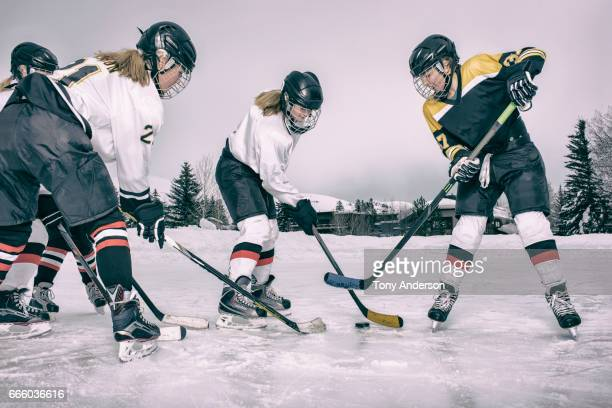 Teenage girls playing ice hockey on outdoor rink in winter