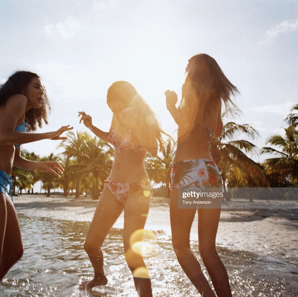 Teenage girls (16-18) playing in water at beach