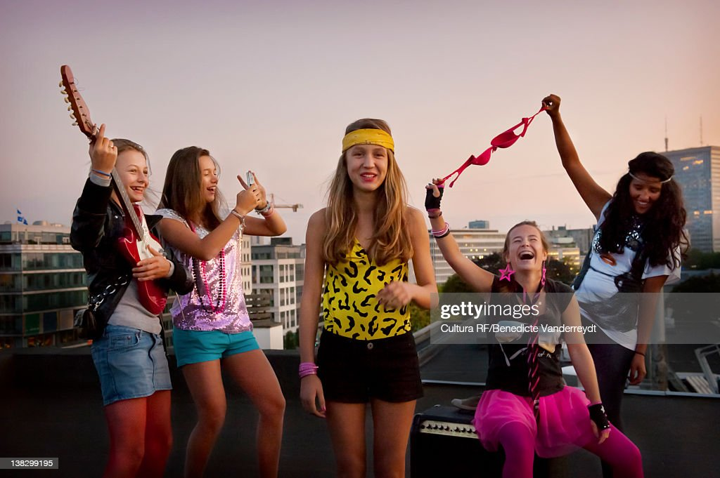 Teenage girls playing music on roof : Stock Photo
