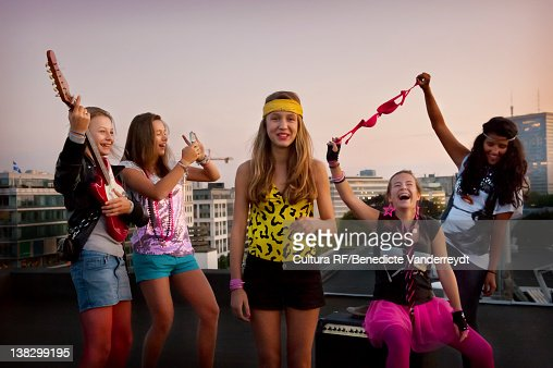Teenage girls playing music on roof : Stock Photo