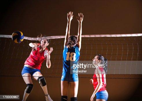 Teenage girls playing volleyball.