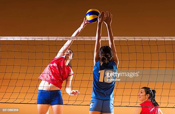 Teenage girls playing volleyball.