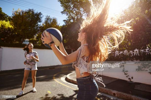 Teenage girls playing with ball in street, Cape Town, South Africa