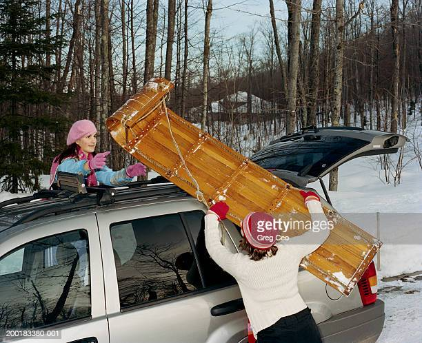 Teenage girls (15-19) putting sled on car roof, winter
