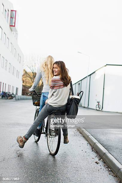 Teenage girls riding bicycle on high school campus