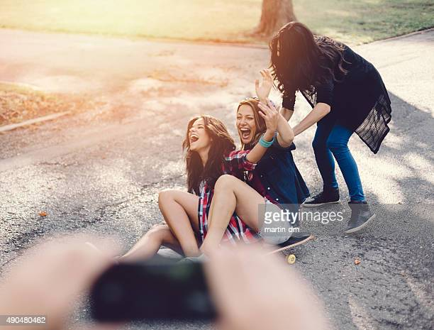 Teenage girls roar with laughter on a skateboard