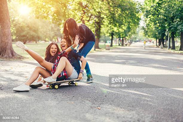 Teenage girls roaring with laughter on a skateboard