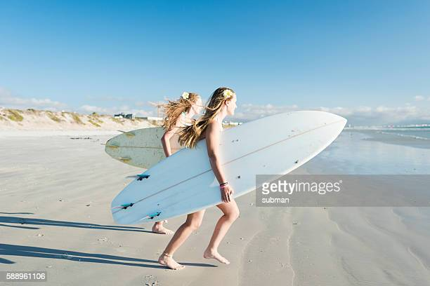 Teenage Girls Running Towards The Ocean With Their Surfboards