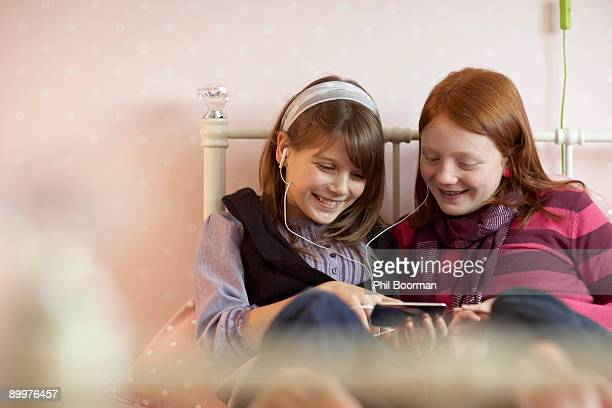 Teenage girls sharing music player