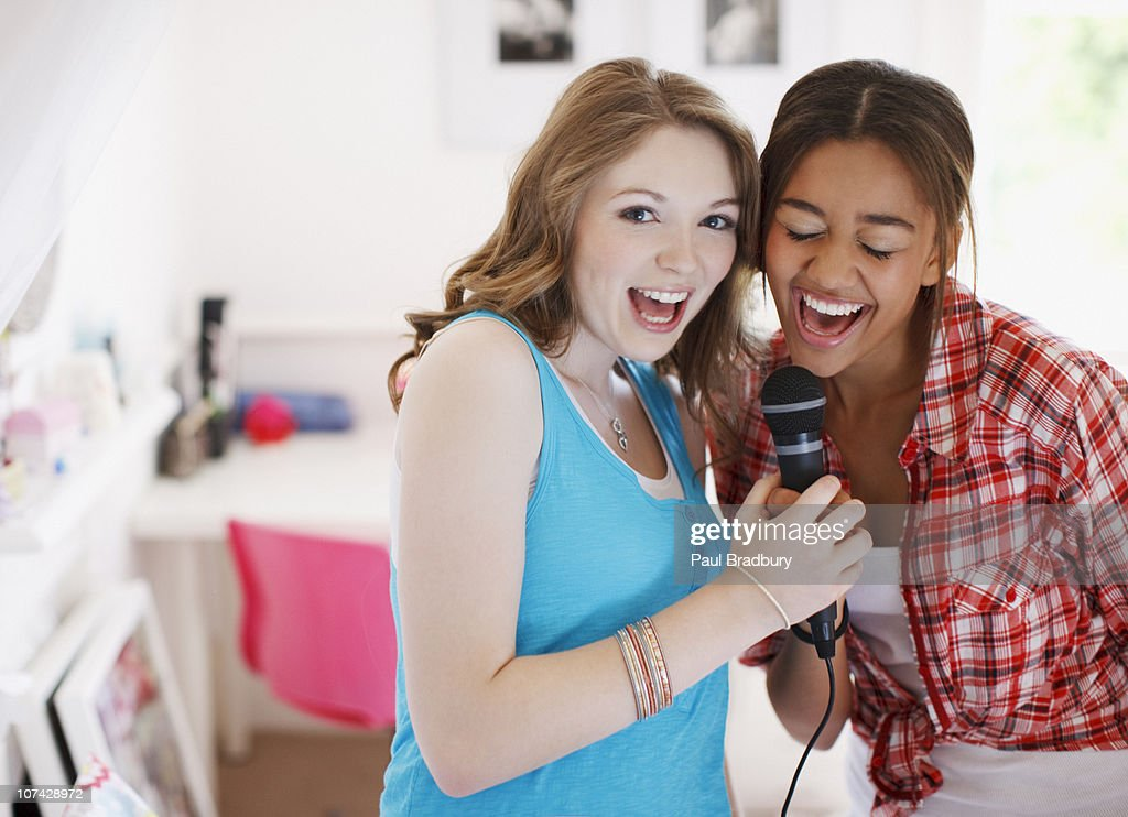 Teenage girls singing into microphone : Stock Photo