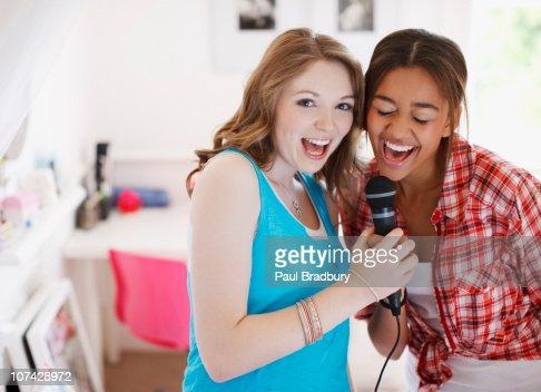 Teenage girls singing into microphone : Stock Photo