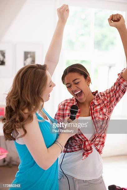 Teenage girls canta en el micrófono
