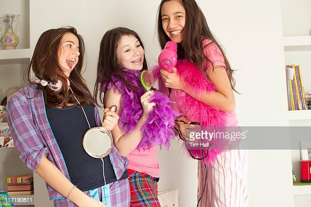 teenage girls singing , wearing pajamas