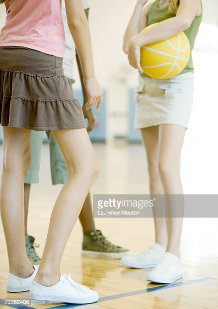 Teenage girls standing in circle, one holding ball, in school gym, chest down
