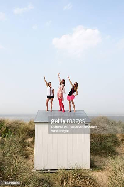 Teenage girls standing on beach hut