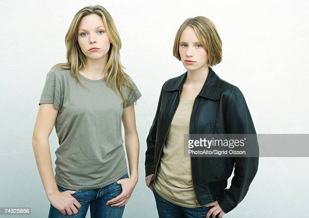Teenage girls standing side by side with hands on hips, looking at camera, portrait