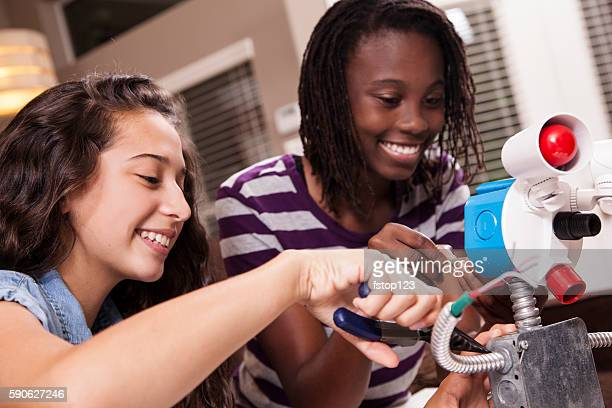 Teenage girls studying science, engineering at home. Homework.