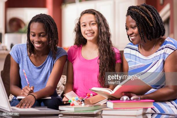Teenage girls studying science with mom at home.