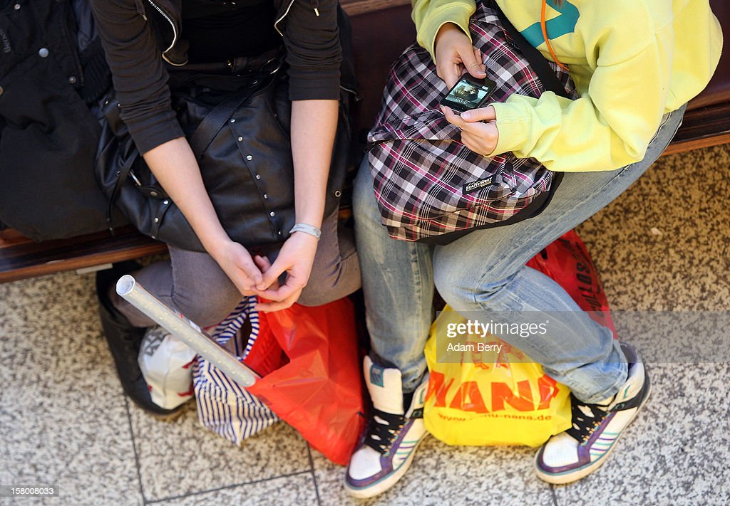 Teenage girls take a break from Christmas shopping at a shopping mall on December 8, 2012 in Berlin, Germany. German consumer confidence dropped prior to the Christmas season from a high level, according to a survey released at the end of November, expecting to harm retail sales in December, but not to the point of hurting businesses greatly.