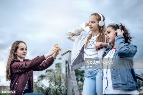 teenage girls taking photo of girlfriends with smartphone