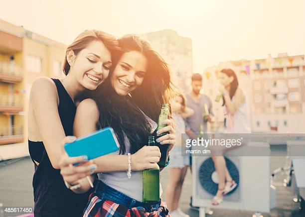 Teenage girls taking selfie on a rooftop party