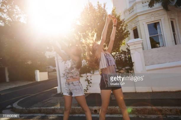 Teenage girls taking selfies in street, Cape Town, South Africa