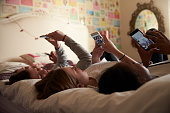 Teenage Girls Using Mobile Phones In Bedroom At Home