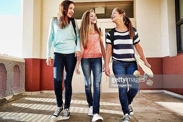 Teenage girls walking on school campus