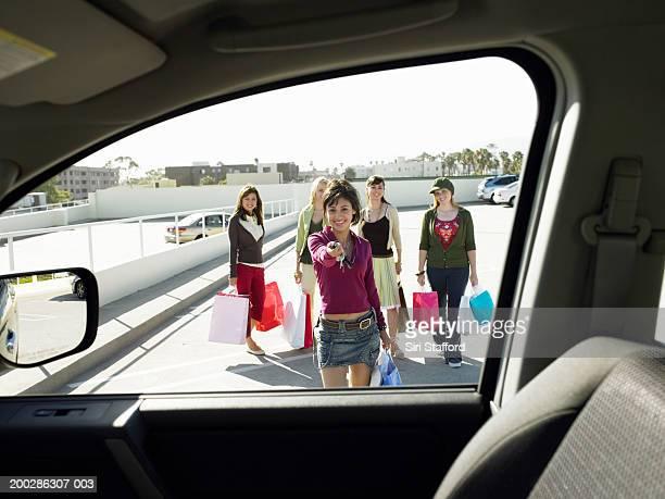 Teenage girls (17-19) walking to car,  one holding door remote