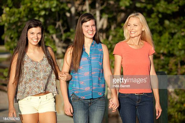 Teenage girls walking with mother