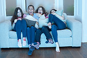 teenage girls watching tv on sofa