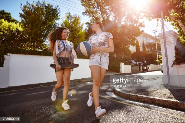 Teenage girls with ball and skateboard in street, Cape Town, South Africa