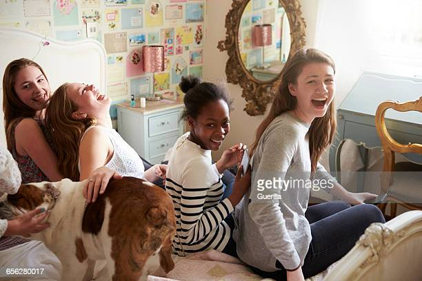 Teenage Girls With Pet English Bulldog In Bedroom At Home