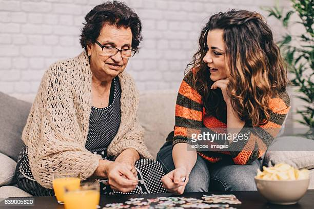 Teenage Granddaughter Helping Grandmother With Puzzle