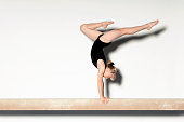Young Gymnast Doing Handstand on Balance Beam