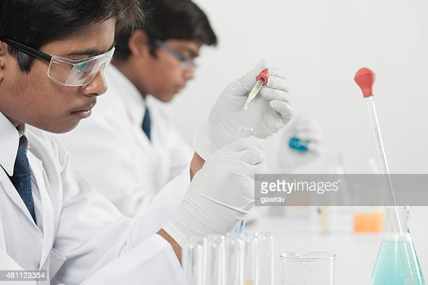Teenage high school science students learning practical chemistry in laboratory.