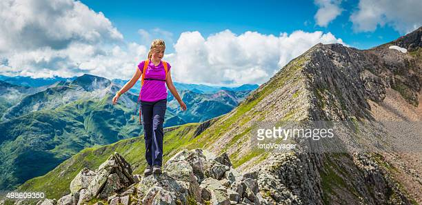 Teenage hiker climbing mountain ridge panorama Ben Nevis Highlands Scotland