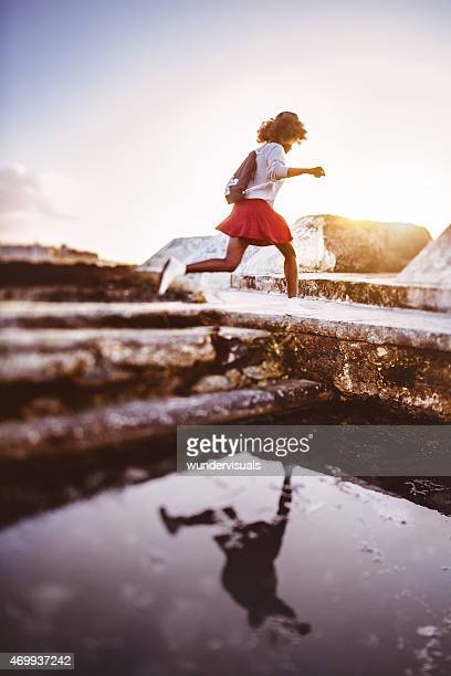 Teenage hipster girl running and jumping at the beach
