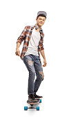 Full length portrait of a teenage hipster riding a longboard isolated on white background