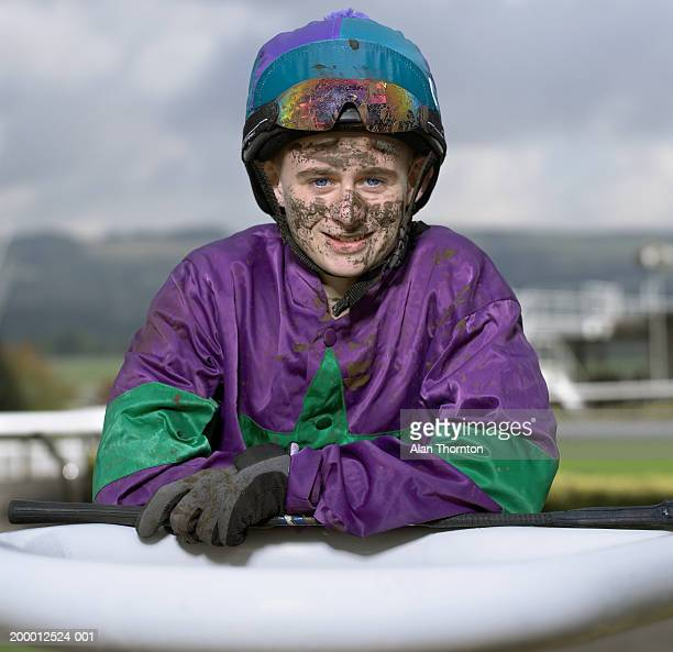 Teenage jockey (16-18) with dirty face, portrait