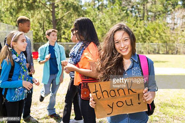 Teenage Latin girl holds 'Thank You' sign in park.