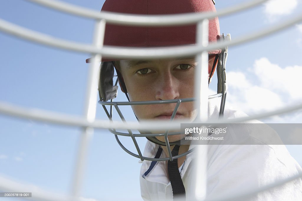 Teenage male cricketer (13-15), view through guard on safety helmet : Stock Photo