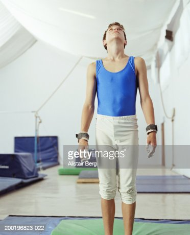 Teenage male gymnast (14-16) on mat in gymnasium, looking up : Stock Photo