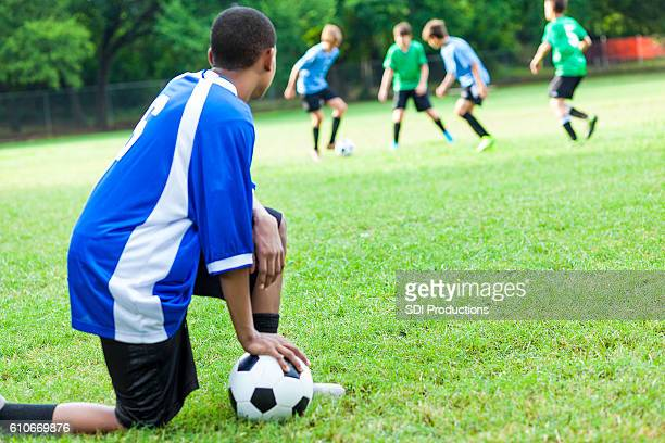 Teenage male soccer player taking a break during practice