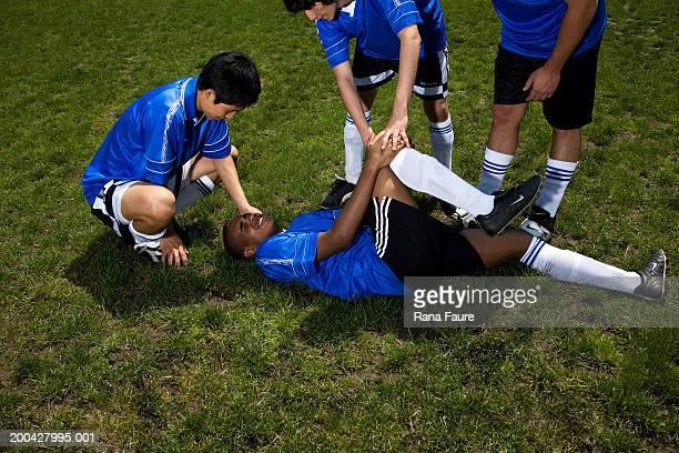 Teenage male (16-20) soccer players helping injured teammate