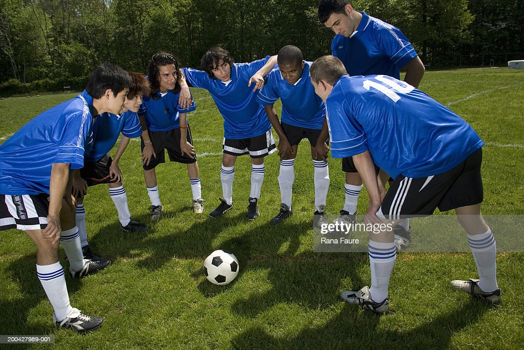 Teenage male (16-20) soccer players in huddle : Stock Photo